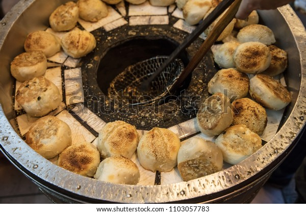 Taiwanese black pepper buns baking on oven in a street night market