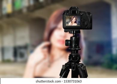 Taiwanese Chinese Vlogger posing for social media  photos viewed through back of camera