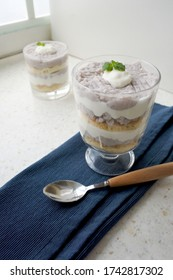 Taiwanese dessert in a glass with taro, layer cake and vanilla yogurt cream mousse. Sweet homemade taro layer cake in a glass.  TaroTrifle in a glass. Light background. Close-up. Free space to place t