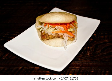 Taiwanese food concept : Fish Bao bun in white plate on dark brown wood table