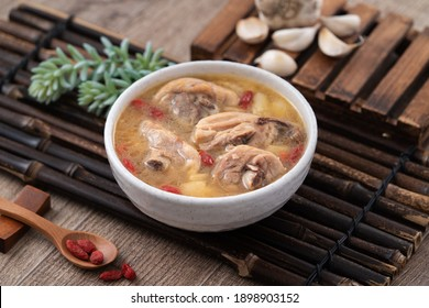 Taiwanese food - Homemade delicious garlic chicken soup in a bowl on dark wooden table background.