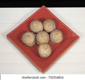 Taiwanese taro mooncakes on a red plate against a white wood and black background.  Mooncakes are eaten during the Asian Mid-Autumn Moon Festival.
