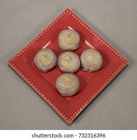 Taiwanese taro mooncakes popular for the Asian Mid-Autumn Moon Festival arranged on a bright red plate against a light brown background.