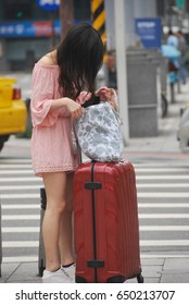 A Taiwanese teenage girl is searching for something in her bag at a pedestrian crossing in Taipei, Taiwan