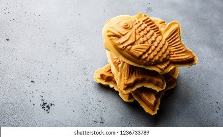 Taiyaki Japanese street food fish-shaped sweet filling waffle on concrete background copy space