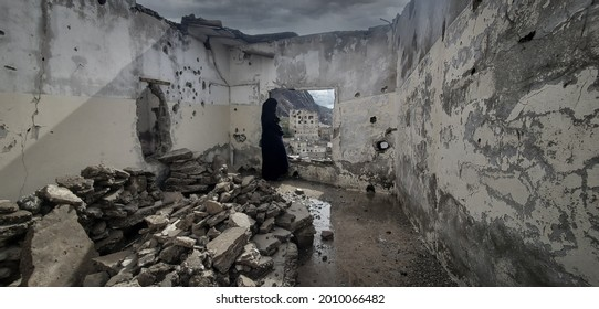 Taiz _ Yemen _ 03 May 2021 : A Yemeni woman stands in a house destroyed by the ongoing war in the city of Taiz, Yemen