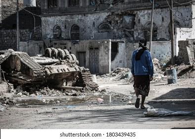 Taiz _ Yemen _ 05 Dec 2016: A young Yemeni man walks amid the destruction caused by the war in the city of Taiz, Yemen