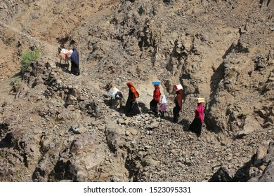 Taiz / Yemen - 02 Apr 2017: Women bring their food and drink needs through rugged mountain roads because of  Al-Houthi militia siege of the villages of Jabal Habashi District in the  west of Taiz City