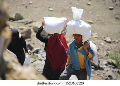 Taiz / Yemen - 02 Apr 2017: Women and children bring their food and drink needs through rugged mountain roads because of  Al-Houthi militia siege of the villages of Jabal Habashi District in the  west