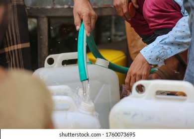 Taiz / Yemen - 20 June 2020 : A Yemeni collects water due to the water crisis and the difficult living conditions that residents of the city of Taiz have witnessed since the beginning of the war