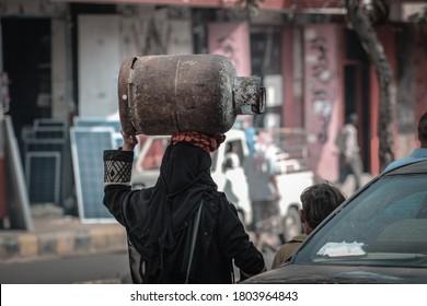 Taiz / Yemen - 30 July 2016  :A Yemeni woman carrying household gas on her head due to the war and the siege on the city of Taiz, Yemen