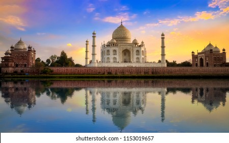 Taj Mahal Agra with Mughal architecture gateway at sunset with water reflection.
