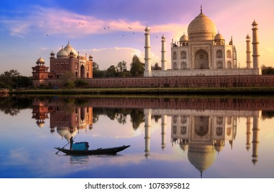 Taj Mahal Agra at sunset with moody sky with wooden boat on river Yamuna
