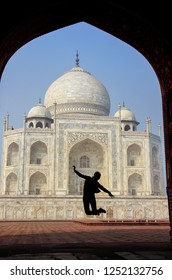 Taj Mahal framed with the arch of jawab with silhouetted woman jumping, Agra, India. Taj Mahal was commissioned in 1632 by the Mughal emperor Shah Jahan to house the tomb of his wife Mumtaz Mahal.
