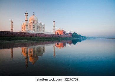 The Taj Mahal glowing red at morning sunrise along the rear riverbank of the holy Jamuna river in Agra, India. Horizontal copy space