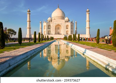 Taj Mahal on a bright and clear day at sunset, reflects in the pond.