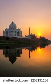Taj Mahal reflected in Yamuna river at sunset in Agra, India. It was commissioned in 1632 by the Mughal emperor Shah Jahan to house the tomb of his favourite wife Mumtaz Mahal.