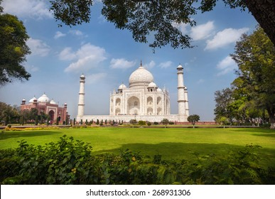 Taj Mahal tomb and green grass at blue cloudy sky in Agra, Uttar Pradesh, India