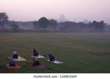 Taj Mahal the wonder of the world and the pride of India in winter early morning warm hazy light with five local people doing Yoga exercises in a garden in the foreground Agra Uttar Pradesh India Asia