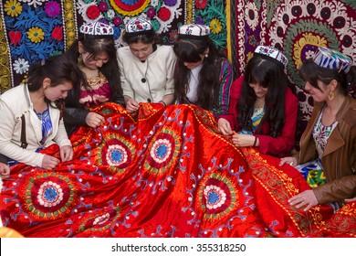 TAJIKISTAN, KHUJAND, 21 MARCH 2015: Tajik girls embroider beautiful carpet in Central Park Navruzgoh during the celebration of Nowruz (New Year) in the city of Khujand, Tajikistan Republic