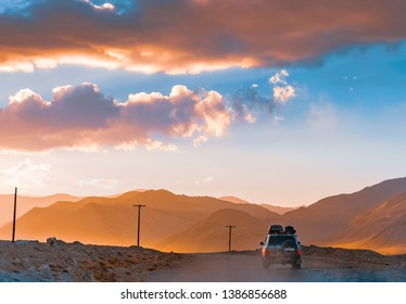 Tajikistan, Murghab. July 12, 2018. Toyota Land Cruiser 100 on a mountain road. Mountains in the rays of the setting sun. Dawn haze. The landscape of rocks.