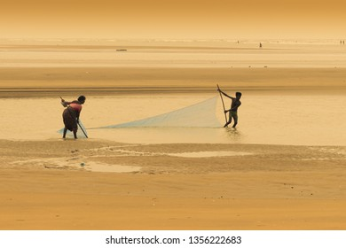 TAJPUR, WEST BENGAL, INDIA - JUNE 22ND, 2014 : A fisherman's wife and son catching fish with fishing net at seashore of Bay of Bengal in the morning. Fishing is livelihood for many people at Tajpur.