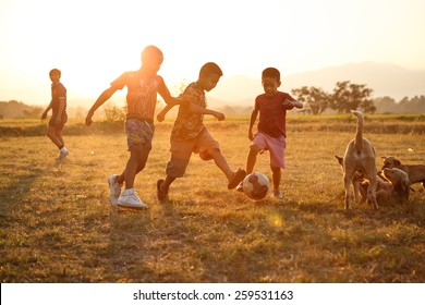 TAK, THAILAND - MARCH 20, 2015:Rural children are playing football in the sunshine day in a village in Tak, Thailand