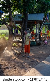 Tak ,Thailand - October 24, 2011. Early sunny morning in the temple. Monks and novices of the monastery sweeping the temple grounds.