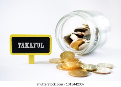 TAKAFUL word on mini chalkboard with golden coins. Islamic banking concept