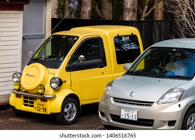 Takayama, Japan - April 9, 2019: Gifu prefecture in Japan with small yellow car parked in mountain town village with midget sign