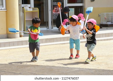 TAKAYAMA, JAPAN - June 4, 2018. Little Japanese boys are playing together with plastic scoops in outdoor playground of kindergarten, while parents are working. And father says goodbye to daughter.