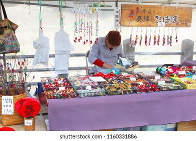 TAKAYAMA, JAPAN - June 5, 2018. Japanese woman is selling handmade puppets, happiness amulets, souvenirs and home decorations at the flea market in urban city street. Made in Japan.