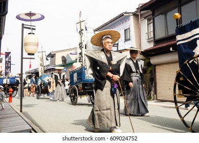 Takayama, Japan - October 10, 2015: Local people in traditional costumes marching the streets of historic Takayama during the annual Takayama Autumn Festival parade