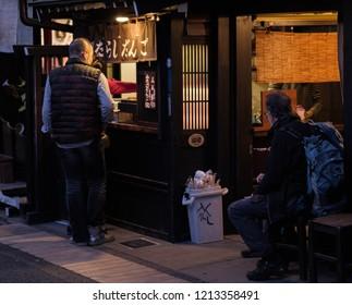 TAKAYAMA, JAPAN - OCTOBER 23RD, 2018.  Tourists walking and exploring the old Sannomachi street at dusk.