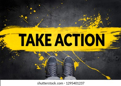 Take Action motivational call top view of sneakers on the concrete flooring with yellow paint stains.