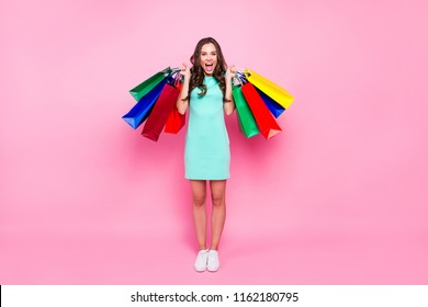 I take it all! Full length, legs, body, size portrait of charming, lovely, cute, sweet brunette girl with long dark hair holds colorful shopping bags isolated on vivid pink background