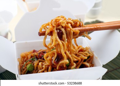 Take away BBQ egg noodles on chopsticks in a take away container.