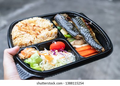 Take away a bento box of grilled Saba fish, grilled vegetables, salad, garlic fried rice and kimchi on hand; easy meal with healthy food.