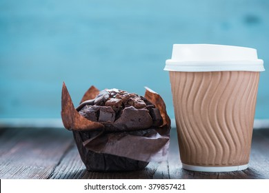 Take away coffe and chocolate muffin on wooden background with copy space for text or advert