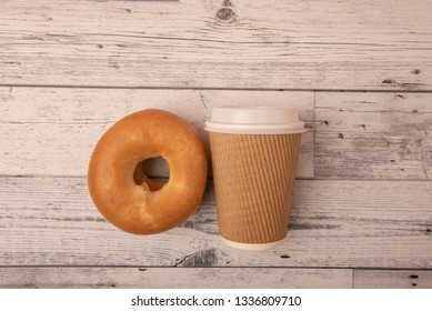Take away coffee cup with bagel on wooden background