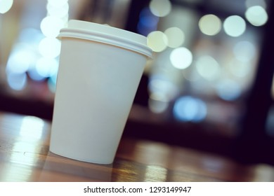 take away coffee cup empty blank copy space for your design text or banner of brand, hot drink on wood table in cafe shop restaurant with beautiful light decoration, image used retro vintage filter