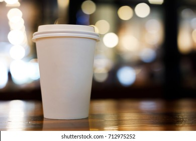 take away coffee cup empty blank copy space for your design text or banner of brand, hot drink on wood table in cafe shop restaurant with beautiful light decoration party