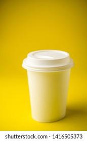 Take away coffee on yellow background
