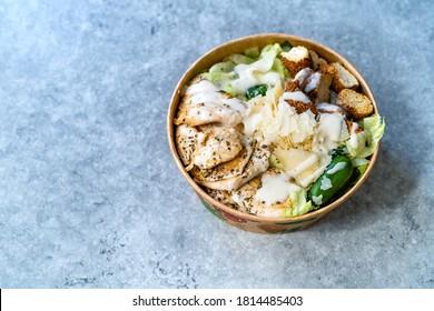 Emporter une salade de ceaser biologique saine avec du poulet, du fromage parmesan, du pain de Crouton et de la sauce Mayonnaise au yaourt.