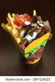 Take away kebab box with meal and vegetables with french fries and garlic dip.