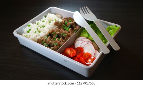Take away meal with rice, meat and salad. Meal prep on dark background. Ready to eat lunch with plastic knife and fork.