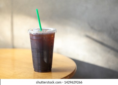 Take away plastic cup of iced black coffee Americano on wooden table with morning sunlight