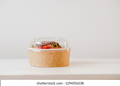 Take away salad in disposable craft paper bowl on white background. Minimalism food photography concept. Mockup, copyspace