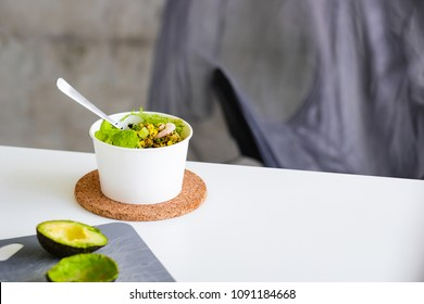 Take away salad in disposable white paper bowl on white table. Minimalism food photography concept. Mockup, copyspace, horizontal