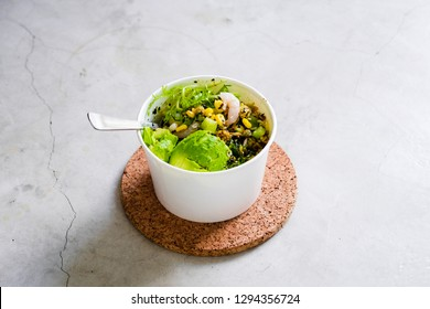 Take away salad in disposable white paper bowl on concrete background. Minimalism food photography concept. Flatlay, copyspace, horizontal